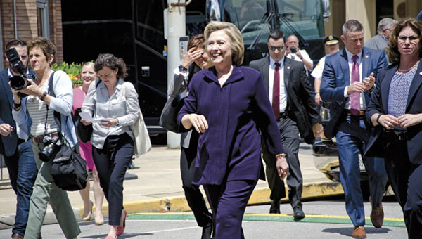 Democratic presidential candidate Hillary Clinton walks up 15th Street in Ashland to meet with supporters prior to her roundtable discussion on jobs at Alma's Italian Restaurant on Monday.