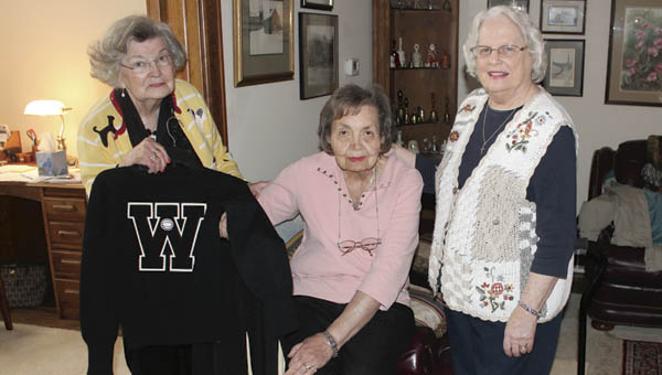 Anna Lou Coburn Robinson, left, holds her Waterloo Wonders cheerleading uniform at the home of Georgia Hairston Triplett, a former cheerleader and sister of Wonders coach Magellan Hairston, center. Robinson donated the uniform to the Lawrence County Museum and presented it to trustee Kay Rader, right.