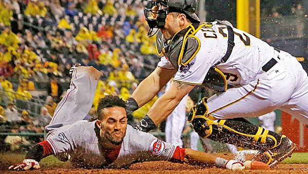Cincinnati Reds' Billy Hamilton (left) slides safely across home plate ahead of the tag by Pittsburgh Pirates' catcher Francisco Cervelli in the fifth inning. The Reds beat the Pirates 6-5 in 11 innings on Sunday. (Courtesy of the Cincinnati Reds.com/Gene J. Puskar (AP))