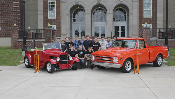 The Ironton High School Auto Tech class stands with the top winning cars from its car show in April. The car on the left won Judge's Choice, while the truck took Students' Choice.