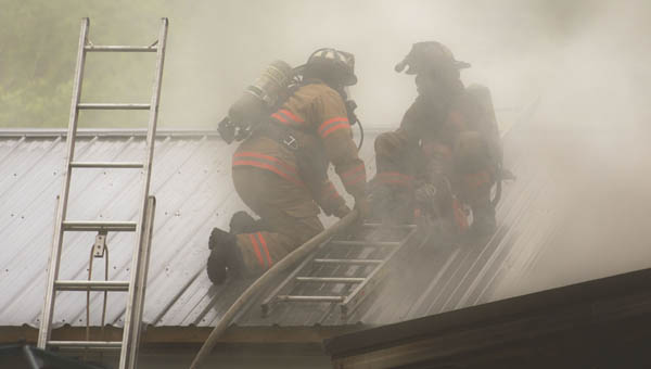 Firefighters work to put out a house fire on County Road 119 Thursday afternoon.