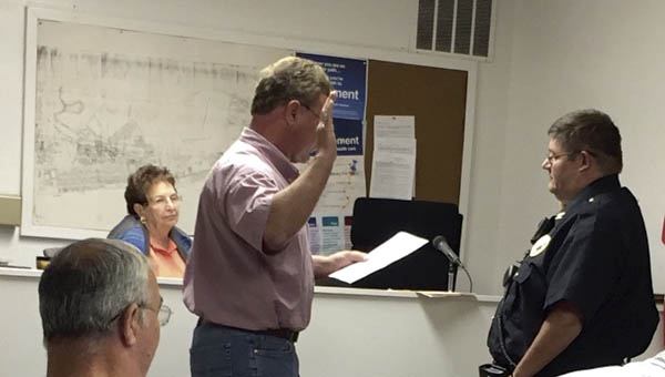 Chesapeake Mayor Tommy Templeton swears in Lenny Abrams as the village's new police chief at a meeting of council on Monday.