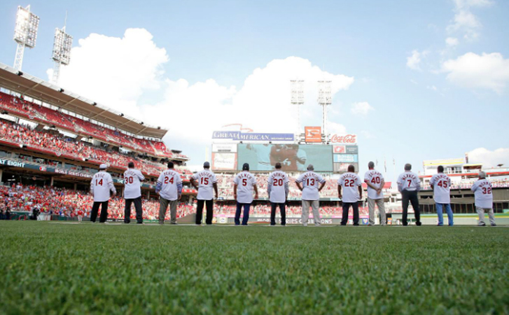 Members of the 1976 World Champion Cincinnati Reds lined up along the first base line before Friday's game as they were honored with a 40th reunion. Player are watching a tribute to the team that was played on the scoreboard. (Photo Courtesy of The Cincinnati Reds.com/Kirk Irwin – Getty Images)