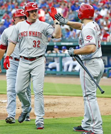 The Cincinnati Reds' Jay Bruce (32) celebrates his three-run home run with Adam Duvall against the Texas Rangers during the first inning on Tuesday at Globe Life Park in Arlington, Texas. The Reds beat the Rangers 8-2. (Jim Cowsert/Fort Worth Star-Telegram/TNS)
