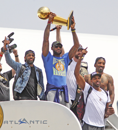 Cleveland Cavaliers' LeBron James holds up the NBA Championship trophy alongside teammates on Monday after arriving in Cleveland, Ohio. Joining James are Kyrie Irving, left, Kevin Love, J.R. Smith and Tristan Thompson as they arrive at Atlantic Aviation. (Mike Cardew/Akron Beacon Journal/TNS)