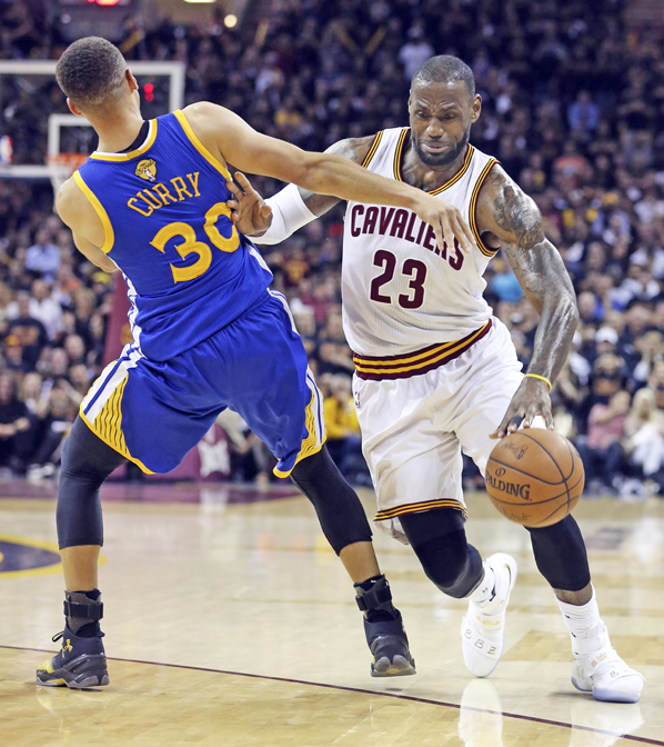 The Cleveland Cavaliers' LeBron James (23) drives against the Golden State Warriors' Stephen Curry (30) during the first quarter in Game 6 of the NBA Finals on Thursday. The Cavaliers won 115-10 to force a Game 7. (MCT Direct/Phil Masturzo – Akron Beacon Journal – TNS)