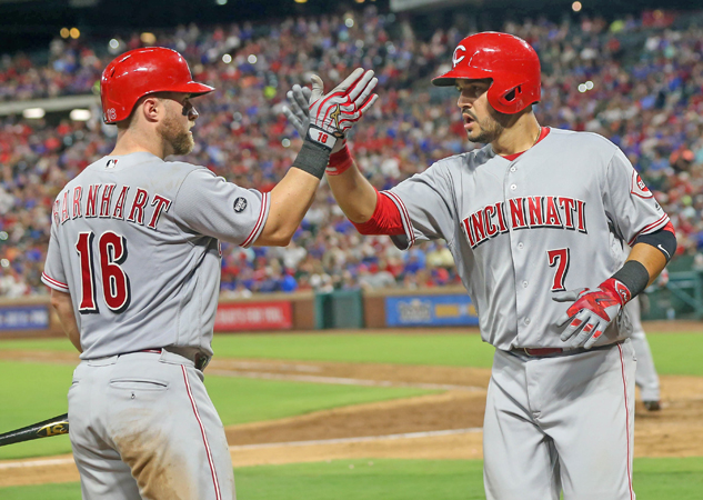The Cincinnati Reds' Eugenio Suarez (7) is congratulated by teammate Tucker Barnhart after hitting a three-run home run in the eighth inning against the Texas Rangers on Wednesday at Globe Life Park in Arlington, Texas. The Rangers won, 6-4. (Steve Nurenberg/Fort Worth Star-Telegram/TNS)