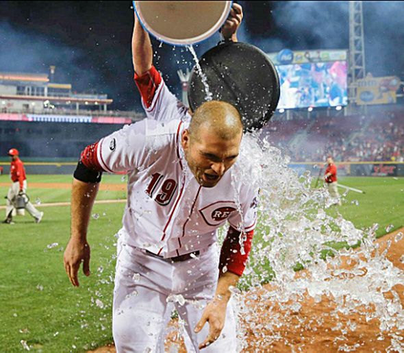 Cincinnati Reds' first baseman Joey Votto is doused with a water cooler by teammate Ivan De Jesus Jr. after hitting a walk-off home run on Tuesday in a 7-6 win over the St. Louis Cardinals. (Photo Courtesy of The Cincinnati Reds.com/John Minchillo — AP)
