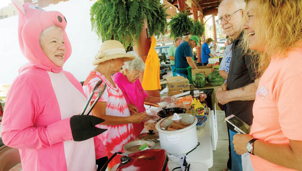 Lois Terkhorn, left, greets guests to the Harvest for the Hungry Booth as she and other volunteers raise money for the food pantry Saturday at the Ironton Farmers Market.