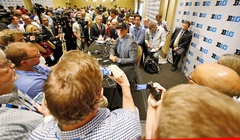Michigan Wolverines head football coach Jim Harbaugh (seated) addresses the Big Ten media during the first day of the conference media days on Monday. (Photo Courtesy of Big Ten.com)