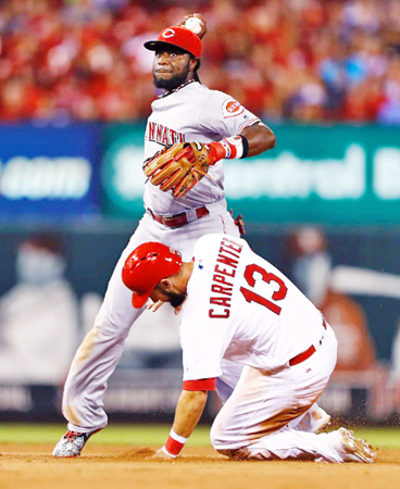 Cincinnati Reds' second baseman Brandon Phillips completes a double play against a sliding Matt Carpenter of the St. Louis Cardinals during the fifth inning of Tuesday's game. The Reds beat the Cardinals 7-4. (Photo Courtesy of The Cincinnati Reds.com/Billy Hurst — Associated Press)