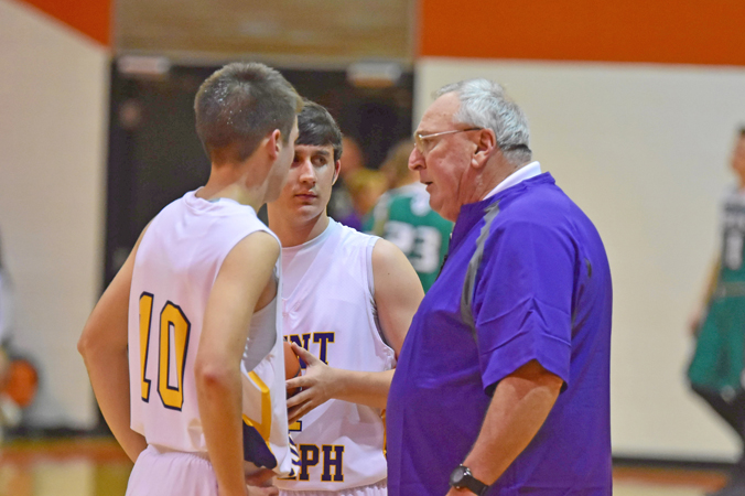 Long-time high school coach Rex Cooksey (right) talks with Tre Neal (10) and Peyton Adkins during a recent game. Cooksey coached in Kentucky for 40 years but came out of retirement this season to take over as the St. Joseph Flyers' head basketball coach. (Kent Sanborn of Southern Ohio Sports Photos)