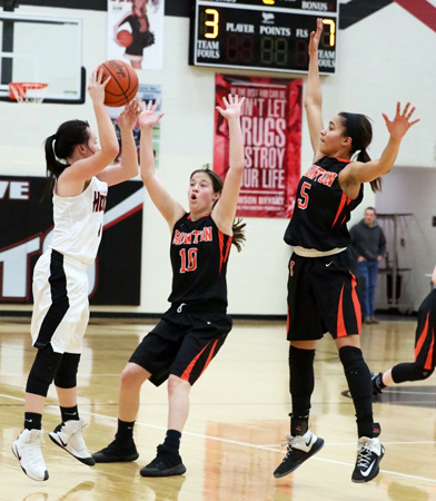 Coal Grove Lady Hornets' Bailee McKnight (left) tries to get a pass over the outstretched arms of Ironton Lady Fighting Tigers' Riley Schreck (10) and Lexi Wise (5) during Thursday's OVC game. Ironton won 49-38 to clinch a share of the league title. (Tim Gearhart of Tim's News & Novelties, Park Ave. in Ironton)